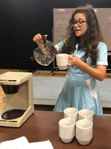 "Singing as she pours coffee, sophomore Sydney Alvarez rehearses for ""I Dreamed a Dream.""   This is one of the three student directs productions."