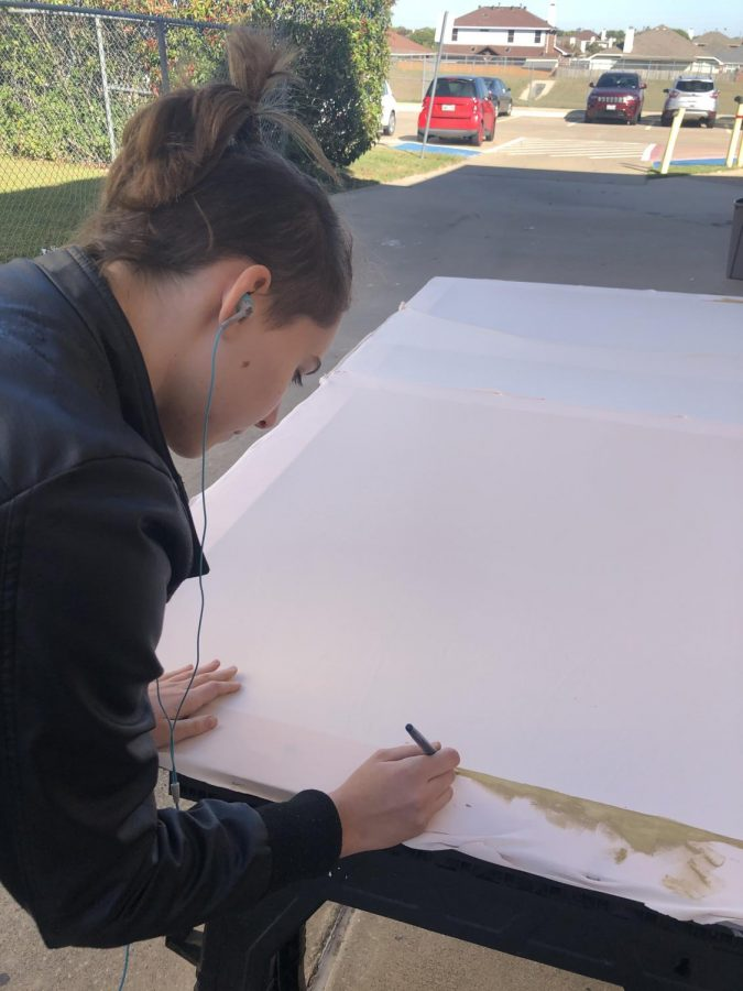 Junior Alicia Pfiefer paints a set piece for the haunted house.