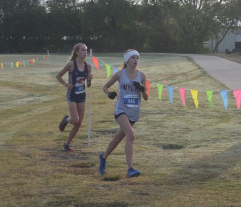 Freshman Ana Eischen attempts to overtake a Wylie runner.  Eischen placed second at the district meet and broke the school record with a time of 19:49.