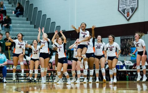 In the third round of the playoffs, the varsity volleyball team reacts after winning the 4th set against Prosper 25-23.