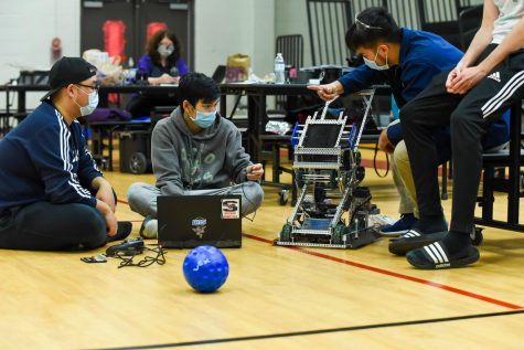 Reborn team members Danny Lee, Thom Pham and Andy Nguyen work on their robot between competition rounds.