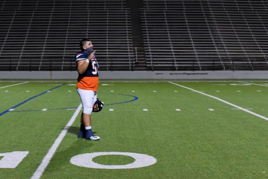 Senior Ricardo Ochoa stands for the alma mater in an almost empty stadium.  Because of COVID-19 restrictions fans were limited to two per game participant.